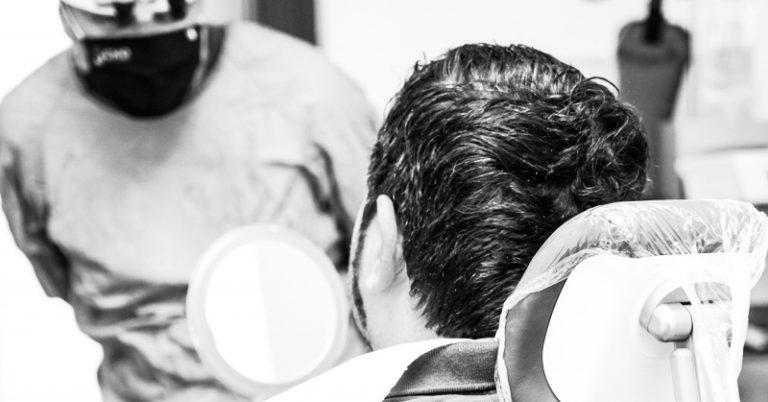 Paziente guarda allo specchio il suo nuovo sorriso con le faccette dentali